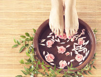 Spa background of beautiful female feet, flowers and petals. Legs, flowers, petals and ceramic bowl. Spa, recreation and skin care concept Royalty Free Stock Photos