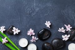 Spa background with massage pebble, green leaves, beautiful flowers and candles on black stone table top view. Aromatherapy. Stock Image