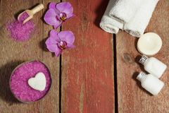 Spa background with orchid, rose bath salt, body lotions and white towels on a wooden table with copy space for your Royalty Free Stock Photos