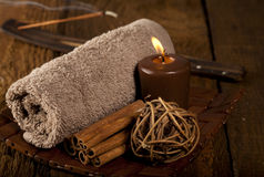 Spa Background. With rolled towel, candle, sticks of cinnamon and incense stick Stock Images