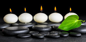 Spa background of row white candles and green leaf on black zen. Stones background with dew, panorama stock images