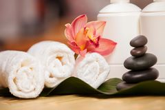 Spa background. White towels on exotic plant, beautiful orchid Stock Image