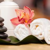 Spa background. White towels on exotic plant, beautiful orchid Stock Photos