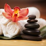 Spa background. White towels on exotic plant, beautiful orchid. Flower and balancing stones for relax spa massage and body treatment. Asian medicine with aroma stock photography