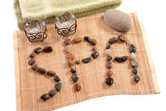 Spa Banner of stones on bamboo. A banner made from stones laid strategically on bamboo matt spelling the word SPA also towel, stone for massage, and candles for Stock Photography