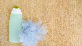 Spa bath concept. Flat lay background washcloth and shampoo on towel. Green bottle. Top view copy space.  stock image