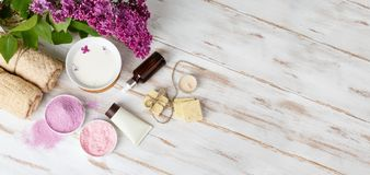 Spa and bath cosmetics with lilac flowers. Bath salt, soap, cream, oil, serum and towel rolls on wooden rustic background. Organic natural cosmetics. Fresh royalty free stock images