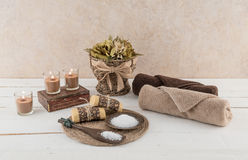 Spa and Bath Essentials with Glowing Candles. Spa and bath essentials, including handmade artisan soap and body scrub, with glowing candles Stock Photos