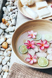 Spa bath for feet. Foot bath in bowl with lime and tropical flowers, organic spa pedicure treatment Stock Photo