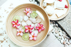 Spa bath for feet. Foot bath in bowl with lime and tropical flowers, organic spa pedicure treatment, top view Royalty Free Stock Image