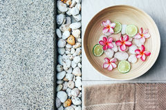 Spa bath for feet. Foot bath in bowl with lime and tropical flowers, organic spa pedicure treatment, top view Stock Images