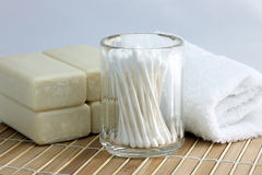 Spa Bath Items. Soap bars, cotton swabs and towel on a bamboo mat stock photography
