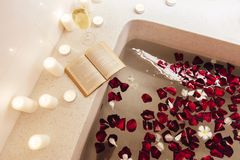 Spa bath with petals and candles. Prepared luxury spa bath decorated with flower petals and candles, top view from above stock photos