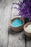 SPA Bath Salt closeup. SPA still life, Bath Salt closeup with violet flowers on wooden background. Desaturated royalty free stock photography