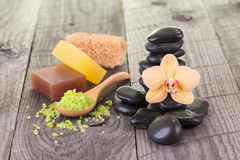 Spa with bath salt, soaps, loofah and black stones Royalty Free Stock Photography