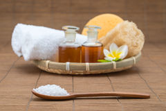 Spa bath, salt spoon, towel sponge essential oil and flower for Royalty Free Stock Photography