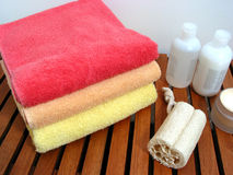 Spa or bathroom accessories. Stack of colorful towels, loofah sponge, lotions, shampoos, creams Royalty Free Stock Photography