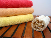 Spa or bathroom accessories. Stack of colorful towels amd loofah sponge on a wooden bench Royalty Free Stock Images