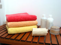 Spa or bathroom accessories. Stack of colorful towels, loofah sponge, lotions, shampoos, creams Stock Photography