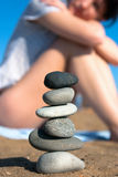 SPA on a beach. Young attractive woman sitting on the beach and looking at the stacked stones Royalty Free Stock Images