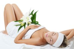 Spa beautiful woman lays with lily Royalty Free Stock Photography