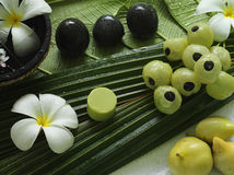Spa beauty. Exotic tropical flowers fruits stons towels  soap on green leaves Royalty Free Stock Image