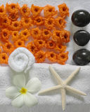 Spa beauty. Exotic tropical flowers starfish stones on white towels Stock Photo