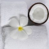 Spa beauty. Exotic tropical flowers coconuts on white towels Stock Image