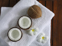 Spa beauty. Exotic tropical flowers coconuts on white towels Royalty Free Stock Photos