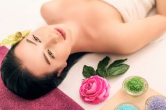 Spa, beauty, people and body care concept - beautiful woman getting face treatment over holidays light background Royalty Free Stock Photo