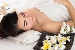 Spa beauty skin treatment woman on white towel. Gorgeous beautif. Ul multiracial Caucasian / Asian female model with perfect skin lying on towel Royalty Free Stock Photography