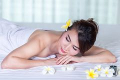 Spa beauty skin treatment woman on white towel. Gorgeous beautif. Ul multiracial Caucasian / Asian female model with perfect skin lying on towel Royalty Free Stock Image