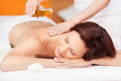 Spa beauty treatment with oil. Beautiful young woman enjoying a spa beauty treatment with an oil based massage stock photo
