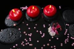 Spa begrepp av röda stearinljus på zenstenar med droppar, orkidé Arkivfoton