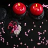 Spa begrepp av röda stearinljus på zenstenar med droppar, orkidé Royaltyfri Bild