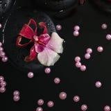 Spa begrepp av röda stearinljus på zenstenar med droppar, orkidé Fotografering för Bildbyråer
