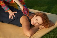 Spa body massage. Smiling brunette getting a relaxing massage poolside outside at the spa Stock Image