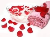Spa bowl with rose petals and cremes. Spa bowl with pink water with rose petals and cremes stock photos