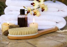 Spa brush. Spa and wellness essentials of scrub brush candles and lotions and orchids Stock Images