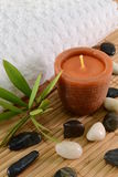 Spa candle concept. Image of spa concept with candle, towels, leaves and stones Stock Photography
