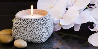 Spa candle setting. With orchid and massage stones Royalty Free Stock Images