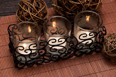 Spa candles. Three candles with wicker balls on dark background Royalty Free Stock Photo