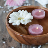 Spa with candles. Spa with salt, gerberas and candles on the wooden table, selective focus and square image Royalty Free Stock Photography