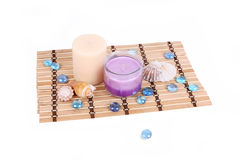 Spa candles with shells on bamboo mat isolated on Royalty Free Stock Image