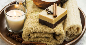Spa-care products with coffee and cinnamon soap, towel and candl Royalty Free Stock Image