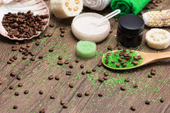 Spa and cellulite busting products on wooden surface. Anti-cellulite cosmetics with caffeine. Wooden spoon with green coarse sea salt and coffee beans, natural stock photo