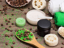 Spa and cellulite busting products on wooden surface. Anti-cellulite cosmetics with caffeine. Wooden spoon with green coarse sea salt and coffee beans, natural royalty free stock image