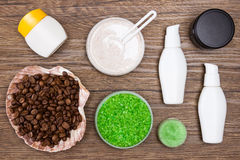 Spa and cellulite busting products on wooden surface. Spa and cellulite busting products. Sea salt, natural scrubs, skin care creams, shell filled with coffee stock image
