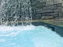 Waterfall on natural stone. Waterfall over natural stone into blue pool in spa Stock Photo