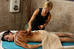 Spa Cocoa Body Scrub. Masseuse applying organic cocoa body scrub to young woman at day spa salon Royalty Free Stock Photography